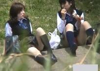 パンチラ盗撮・土手でお股広げて座ってるミニスカ女子校生二人のパンツを狙い対面から隠し撮り